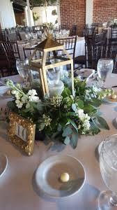 gold lantern centerpiece with greenery at base reception