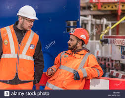 two builders on site in orange safety clothing and hard hats stock