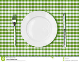 knife white plate and fork on green picnic table cloth stock