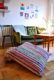 living room with tufted vintage sofa and colorful floor cushions