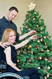 couple decorating a christmas tree together with wife in a