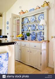 collection of blue white china on fitted cream dresser in country