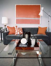 living room grey velvet couch with orange cushions added by
