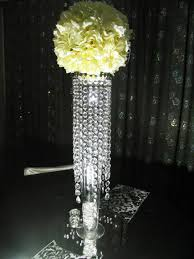 white flowers on the long glass vase with crystal ornaments placed