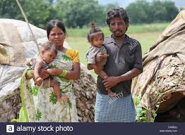 tribal family standing in front of their hut keredari and