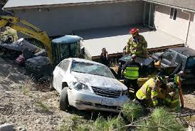 driver hopitalized after rolling car into bucket of a bobcat