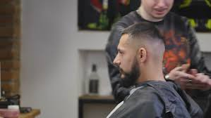 older men getting mohawk haircuts videos barber with old fashioned black razor shaving bearded man stock