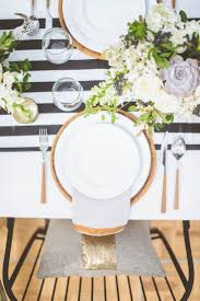 gold plates and cutlery over a black and white table runner my