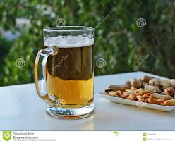 mug of light beer and peanuts on the table stock photo image