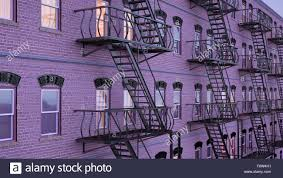 facade of multi family house with fire escape staircases at blue