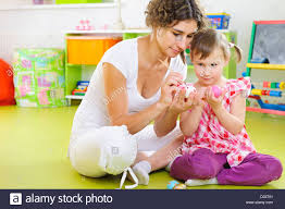 young mother and daughter painting and decorating easter eggs at