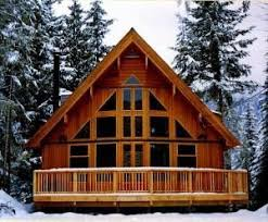 a frame style house chalet style cabin nestled in a forested setting inviting great