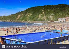 swimming pool in use on a crowded gros beach during mid summer in