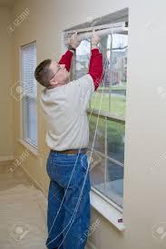 repair man replacing window blinds in apartment making ready