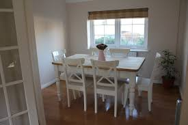 brown wooden top dining tale with carved white wooden legs added