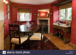 a small cottage dining room with period furniture and vivid red