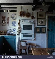 Cottage Pine Furniture by Copper Pans On Wall Above A White Eye Level Oven In A White