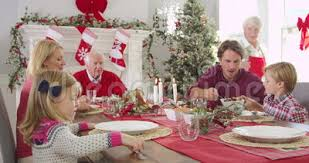 grandmother brings out christmas turkey to family seated around