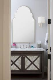brown antiqued mirrored washstand with silver arched mirror