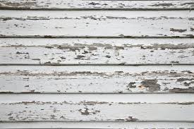 white wood wall with peeling paint background and a closeup