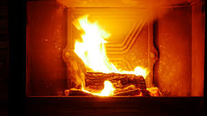 man put big log into fireplace for increasing glowing fire and