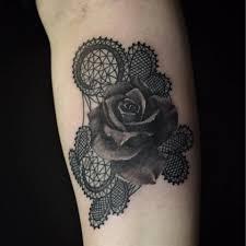 black rose tattoo on the right inner forearm