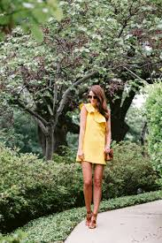 the miller affect wearing a yellow one shoulder dress from