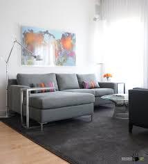 big modern sectional sofa with round glass tabele on dark rug