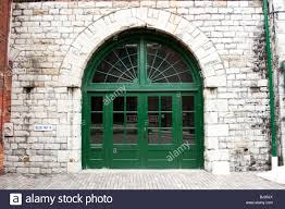 green door entrance to an old white brick building stock photo