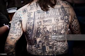 a man has a whole back tattoo with characters from the simpsons