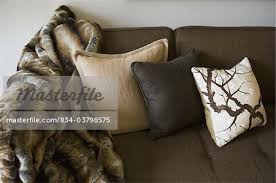 throws and blankets for sofas throw pillows and blanket on brown sofa stock photo masterfile