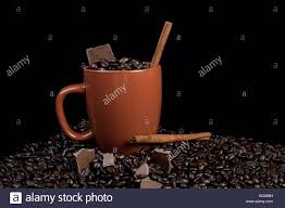 coffee mug full of coffee beans with cinnamon stick sitting on top