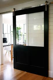 industrial front door black sliding barn door with large glass panel in reading area