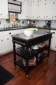 kitchen white kitchen with dark portable kitchen island on