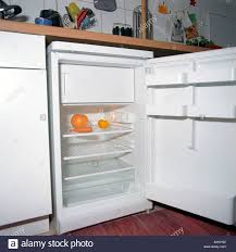 Empty Kitchen View Into An Empty Fridge In Kitchen Containing Only Some Orange