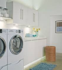 laundry room with white cabinets and led lights the right