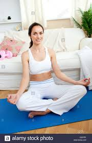 Livingroom Yoga by Concentrated Woman Practicing Yoga In Her Living Room Stock Photo