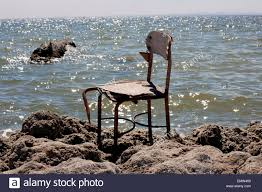 a chair sitting alone on the rocky beach of the salton sea in
