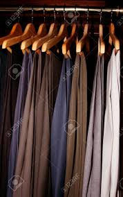 men u0027s dress slacks hanging in a dark wood wardrobe closet stock
