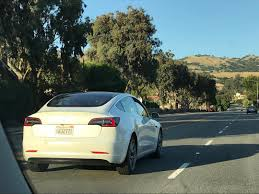 white tesla model 3 spotted with roof rack system installed might