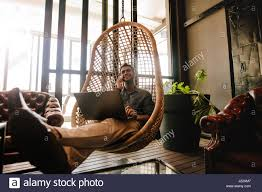 young man sitting on a wicker hanging chair in office lounge with