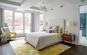 lovely yellow and white bedroom with an armchair and pendant