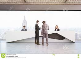 Concrete Reception Desk by People In Office With Reception Desk In New York Stock Photo
