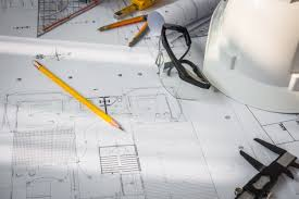 construction plans with white helmet and drawing tools on bluepr