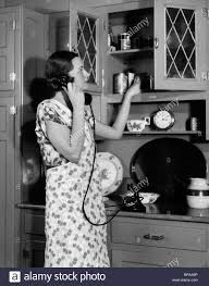 1930s woman housewife wearing apron in kitchen talking on