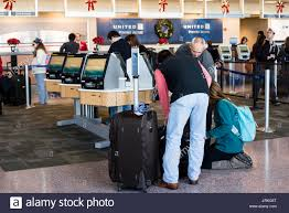 passengers using the united airlines auto check in stations at