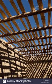 shadows of timber beams and wood ceiling slats on mud brick walls