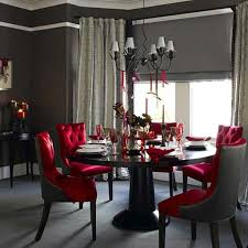 grey wall color and opulent tufted red chairs for glamorous dining