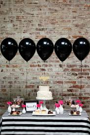 black display table cloth black balloons and a black and white striped tablecloth make for