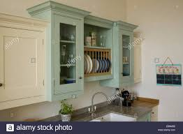 pale green wall cupboard above double sink in country kitchen